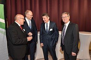 Vier Männer stehen vor einem roten Vorhang. Sie unterhalten sich angeregt und lächeln dabei. Einer von ihnen blickt direkt zur Kamera und lächelt.