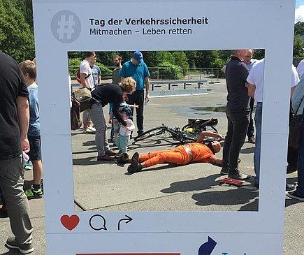 Im Vordergrund steht ein Rahmen aus Karton, auf dem Tag der Verkehrssicherheit steht. Blickt man durch den Rahmen sieht man einen Mensch in orangefarbenem Anzug auf dem Boden liegen. Um ihn herum stehen Menschen. Foto: DVR