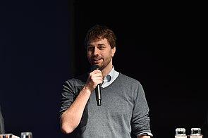 Ein Mann steht auf der Bühne. Er trägt einen grauen Pullover und darunter ein blaues Hemd. In seiner rechten Hand hat er ein Mikrofon, das er knapp vor dem Mund hält.