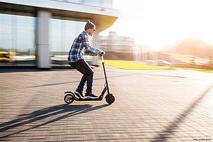 Die Sonne scheint und ein junger Mann fährt auf einem E-Scooter an einem Haus vorbei