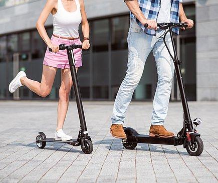 Eine Frau in kurzen rosa Hosen und mit einem weißen Tanktop sowie ein Mann in Jeans und Hemd rechts neben ihr, fahren auf grauen Pflastersteinen auf E-Scootern. Die Atmosphäre ist sommerlich.