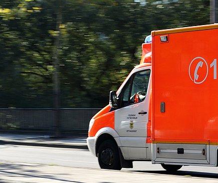 Ein Rettungswagen fährt mit Blaulicht über eine Straße. Die Bäume im Hintergrund sind aufgrund der Geschwindigkeit verwischt.