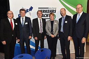 Fünf Männer und eine Frau stehen nebeneinander vor einem Aufsteller. Auf dem Aufsteller sind zwei Logos - Deutsche Verkehrswacht und Deutscher Verkehrssicherheitsrat. Die sechs Menschen lächeln in die Kamera. Die Männer tragen jeweils einen Anzug. Die Frau hat einen Blaser, ein schwarzes T-Shirt und eine schwarze Hose an.