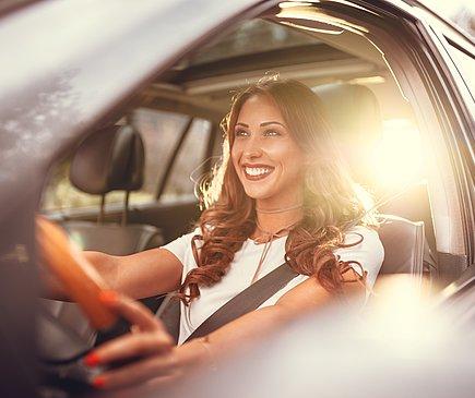 Eine Frau fährt Auto. Sie trägt ein weißes T-Shirt und lächelt. Im Hintergrund geht die Sonne auf.
