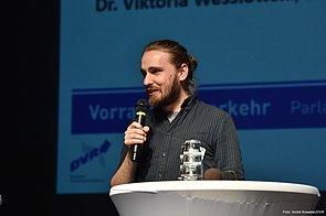 Die Nahaufnahme eines Mannes auf der Bühne. Er trägt ein schwarz-gestreiftes Hemd. Seine braunen Haare sind zu einem Zopf zurückgebunden und er hat einen Vollbart. In der rechten Hand hält er ein Mikrofon. Er steht zwischen zwei Stehtischen von denen jeweils ein Teil der Tischplatte sichtbar ist.