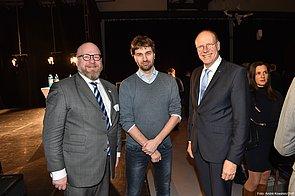 Drei Männer stehen nebeneinander und blicken in die Kamerarichtung. Zwei von ihnen tragen jeweils eine Brille und einen Anzug. Der Mann in der Mitte hat eine Jeans und einen grauen Pullover an.