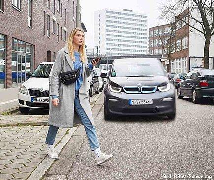 Es ist Herbst. Eine Frau im grauen Mantel und Jeans läuft über die Straße. Sie hält ein Handy in der Hand. Hinter ihr kommt ein Auto angefahren, wobei ihr Blick nicht in Richtung des Autos geht. Sie schaut vielmehr in die andere Richtung, ohne das Auto wahrzunehmen.
