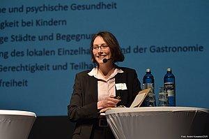 Eine Frau im Hosenanzug steht auf der Bühne. Sie trägt eine Brille und lächelt in Publikumsrichtung. Sie hat ein Kopfmikrofon und hält in der rechten Hand einen Presenter, um von einer PowerPoint-Folie zur nächsten zu wechseln. Mit dem linken Arm stützt sie sich leicht an einem Stehtisch ab, der auf der Bühne steht.