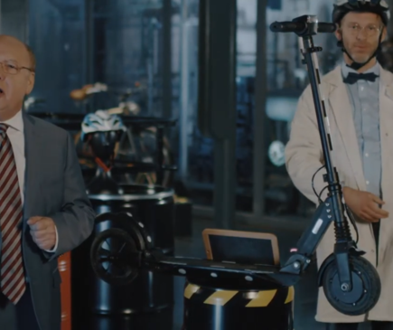 Zwei ältere Männer stehen in einem Keller voller Dinge und mit einem E-Scooter