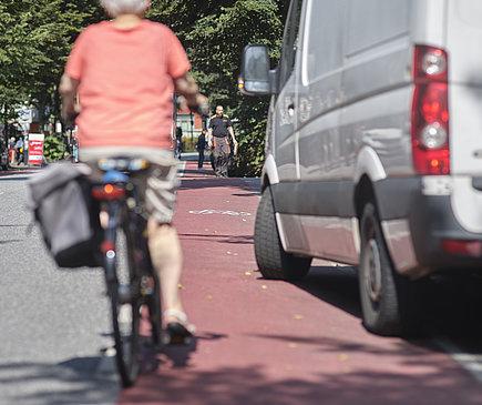 Ein Kleintransporter hält auf einem Schutzstreifen und behindert eine Radfahrerin