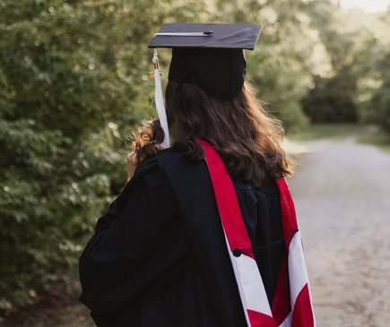 Eine Frau trägt einen schwarzen Talar. Sie steht mit dem Rücken zur Kamera und blickt auf einen Weg, der im Grünen liegt.