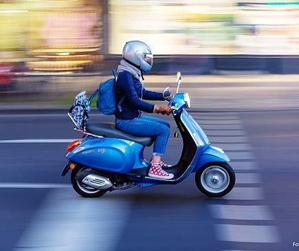 Eine Jugendliche fährt auf einem blauen Moped. Sie trägt einen silberfarbenen Helm und fährt auf einer Straße in der Dämmerung. Der Hintergrund ist verwischt.