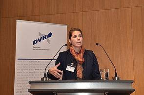 Eine Frau steht an einem Pult mit zwei Mikrofonen
