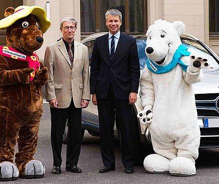 Links steht ein Mensch, verkleidet als Braunbär, daneben ein älterer Herr. Rechts von ihm steht ebenfalls ein Herr in dunklem Anzug, daneben ein Mensch, verkleidet als Eisbär. Im Hintergrund steht ein Auto.