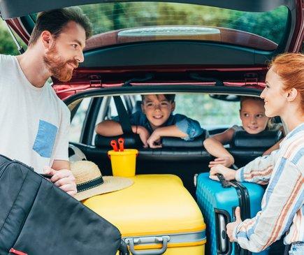An einem geöffneten Kofferraum stehen eine Frau und ein Mann. Gemeinsam laden sie die Koffer ein. Von der Rückbank des Wagens aus lächeln ein Junge und ein Mädchen in die Richtung der Erwachsenen.