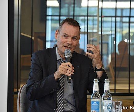 Ein Mann steht hinter einem Tisch und spricht in ein Mikrofon.
