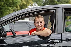 Ein Mann sitzt am Steuer seines Pkw. Das Fenster an der Fahrertür ist geöffnet und er lehnt sich an die frische Luft.