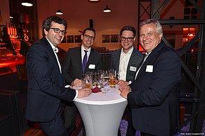 Vier Männer stehen im Halbkreis an einem Stehtisch. Alle lächeln in die Kamera. Sie tragen Anzüge und drei von ihnen haben jeweils eine Brille auf. Auf dem Tisch stehen Bier- und Weingläser. Der Hintergrund ist in abgedunkeltes Licht getaucht.