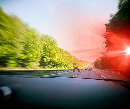 Aus der Perspektive des Auto Fahrenden, der über eine Autobahn fährt, leuchtet am rechten Fahrbahnrand ein rotes Signal (der Blitzer) auf. Es ist ein sonniger Tag.