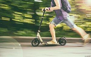 Ein Mann fährt schnell auf einem E-Scooter. Er trägt kurze blaue Hosen, ein lila T-Shirt und einen schwarzen Rücksache. Der Hintergrund ist verschwommen und grün.