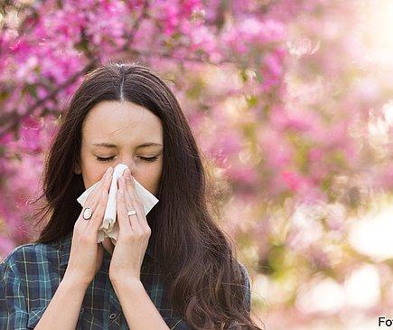 Eine Frau niest in ein Taschentuch. Im Hintergrund stehen blühende Bäume.