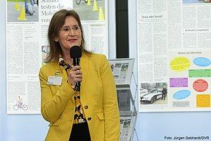 Eine Frau mit gelbem Blazer spricht in ein Mikrofon