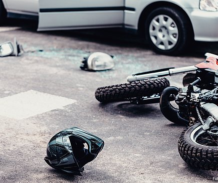 Ein Motorrad liegt rexhts vor einem grauen Pkw. Neben dem Motorrad liegen ein Helm sowie verschiedene Motorradteile.