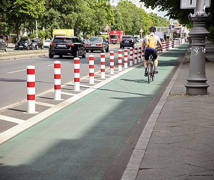Ein grüner Radfahrstreifen ist mit Pollern von der Fahrbahn abgetrennt. Auf dem Weg fährt eine Radfahrer.